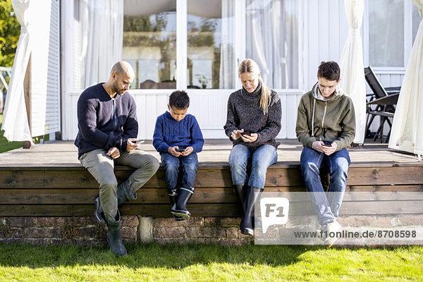 Vierköpfige Familie mit Mobiltelefonen auf dem Hof
