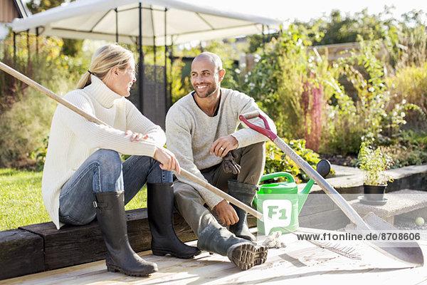 Vollständige Länge des erwachsenen Paares mit Gartengeräten auf dem Hof
