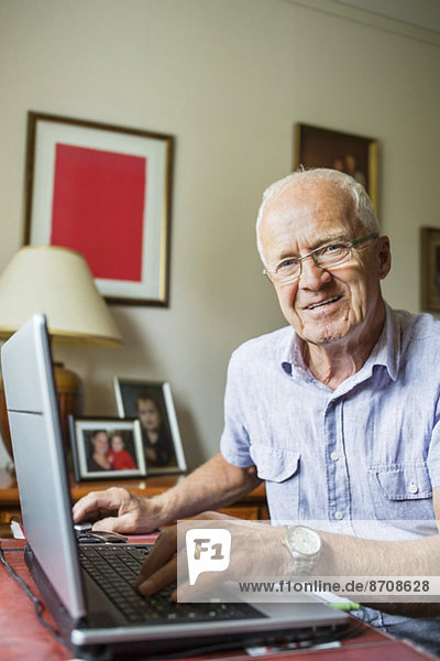 Portrait of smiling senior man using laptop at home