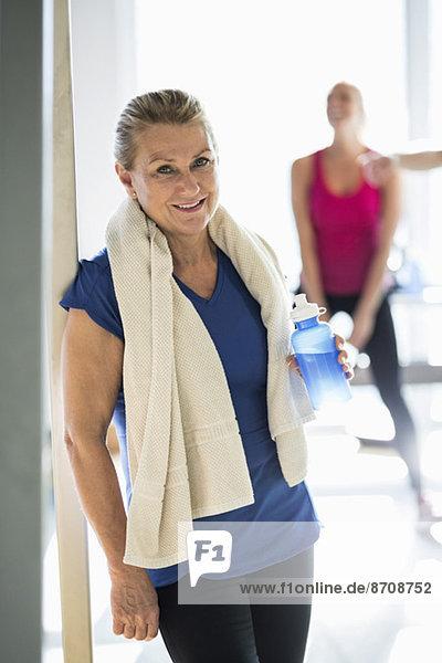Portrait einer fitten Seniorin mit Handtuch und Trinkflasche im Fitnessstudio