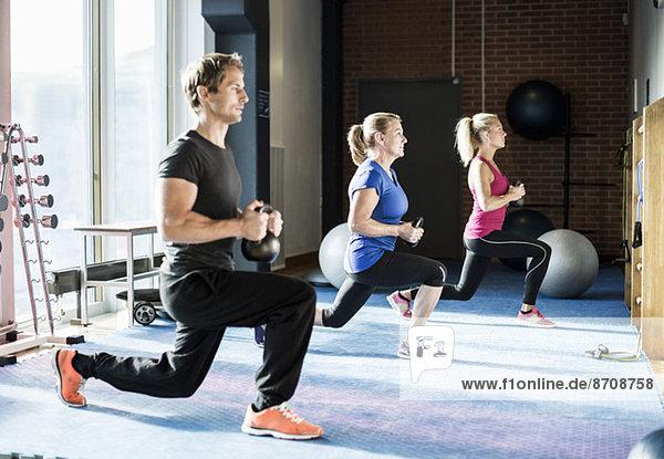 Kunden trainieren mit Kettlebells im Fitnessstudio