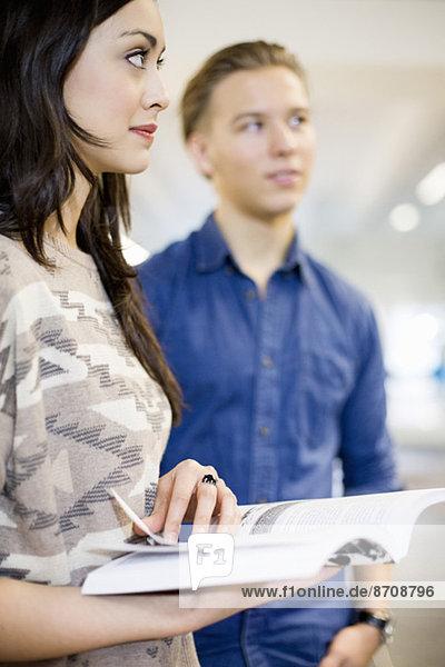Junge Studentin hält Buch mit Freundin im Hintergrund