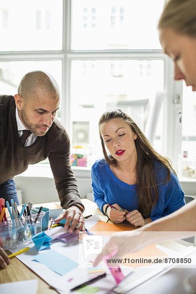 Geschäftsleute arbeiten zusammen am Schreibtisch im Kreativbüro