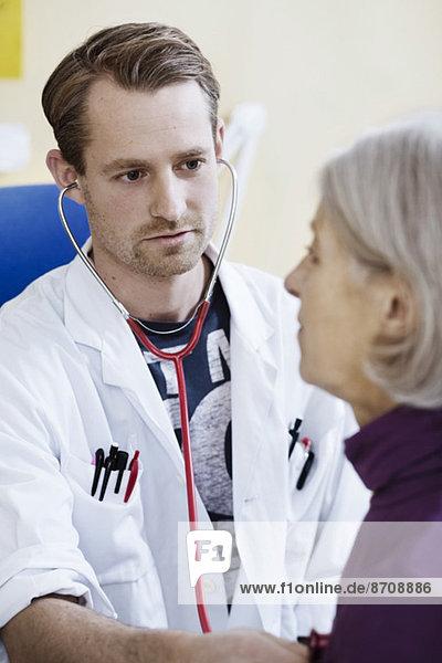 Männlicher Arzt untersucht das Herz der älteren Frau mit Stethoskop in der Klinik