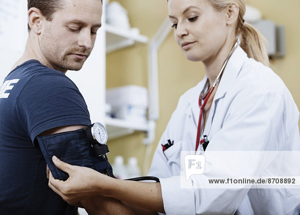 Ärztin wickelt die Manschette an den Arm des Patienten  bevor sie den Blutdruck in der Klinik nimmt.