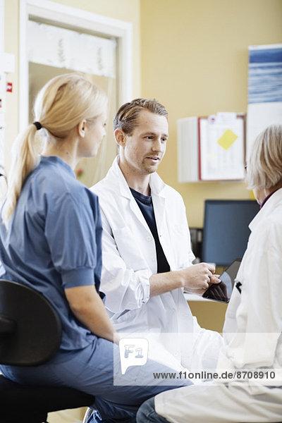 Ärzte und Krankenschwester diskutieren über digitale Tabletten im Krankenhaus