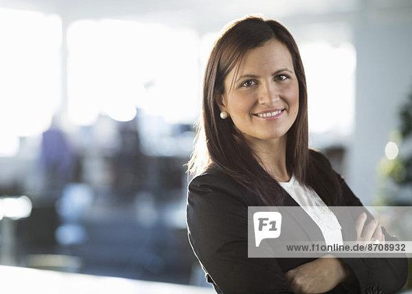 Porträt einer selbstbewussten Geschäftsfrau mit gekreuzten Armen im Amt