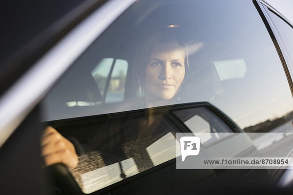 Geschäftsfrau beim Autofahren durchs Fenster schauen