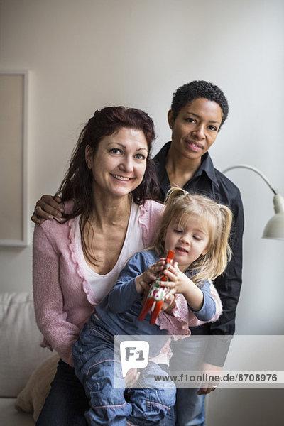 Porträt eines lesbischen Paares mit Mädchen zu Hause