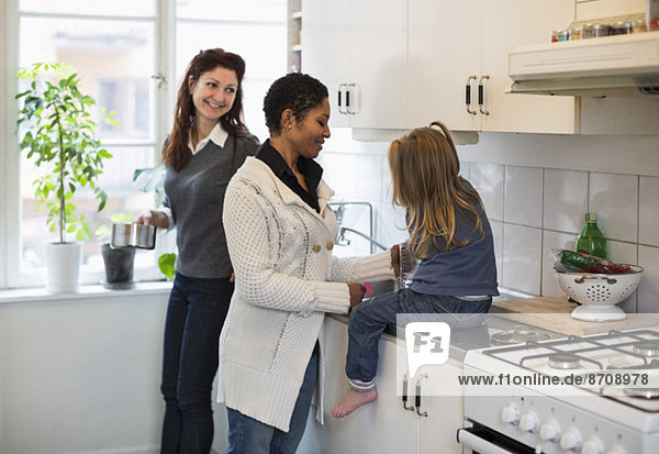 Smiling lesbian couple with girl in kitchen