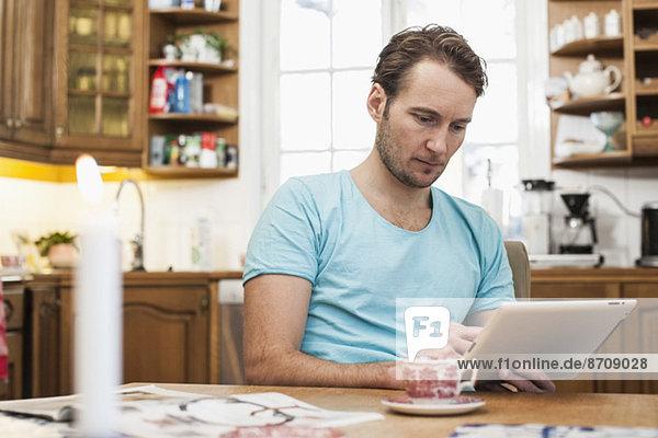 Mann mit digitalem Tablett am Esstisch in der Küche