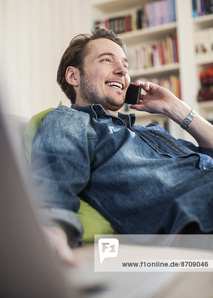Glücklicher Mann mit Handy auf dem Sofa
