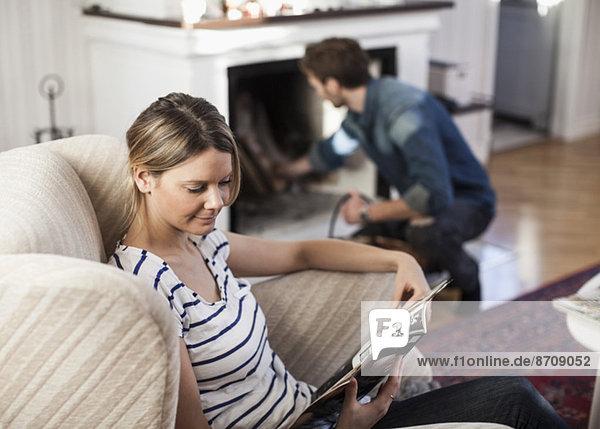 Frau hält Magazin mit Mann  der den Kamin zu Hause setzt