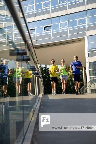 Kleine Gruppe von erwachsenen Läufern über die Stadtbrücke