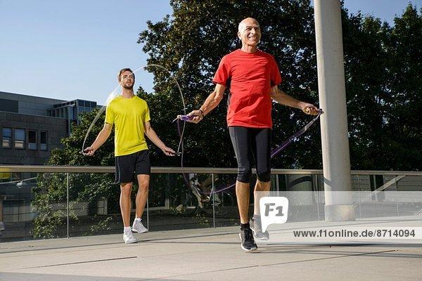 Zwei männliche Athleten trainieren mit Springseilen