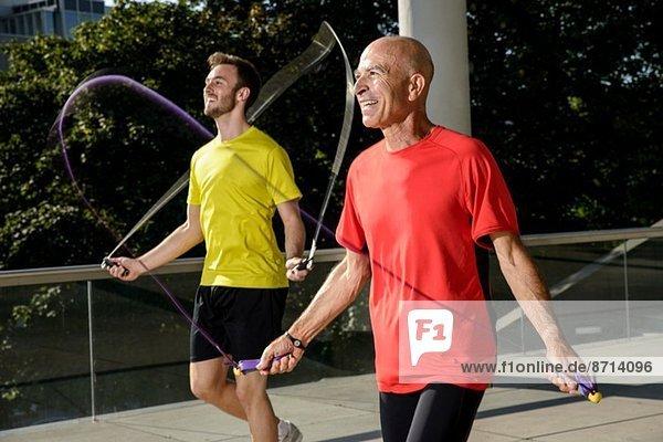Zwei männliche Athleten beim Training mit Springseilen