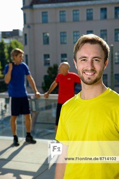 Junge männliche Trainerin und männliche Klasse bei einer Pause auf dem Stadtdach