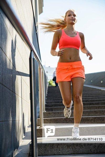 Junge Läuferin bewegt sich die Stadttreppe hinunter
