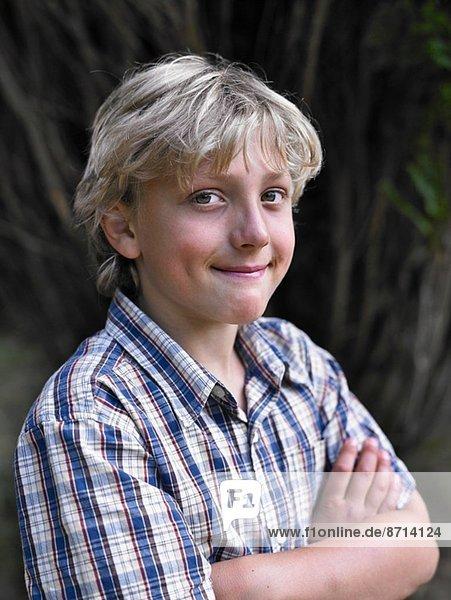 Porträt eines lächelnden Jungen mit gefalteten Armen