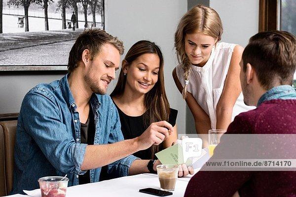 Vier junge erwachsene Freunde sitzen im Café und schauen sich Karten an.