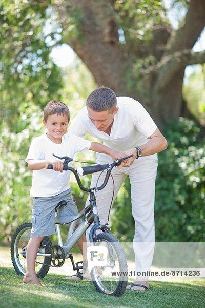 Vater führt den Sohn zum Radfahren