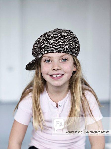 Porträt eines lächelnden süßen Mädchens mit Tweedmütze