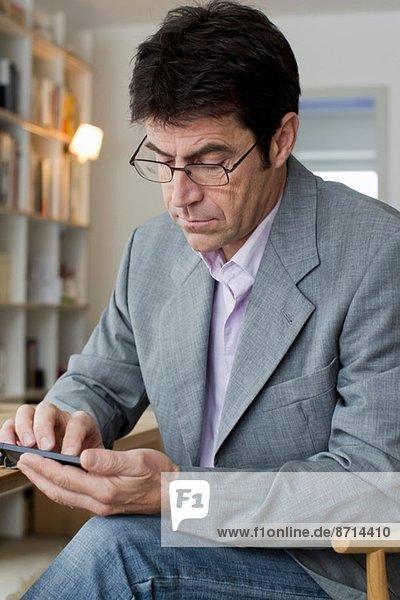 Älterer Mann  der zu Hause arbeitet und auf dem Handy SMS schreibt