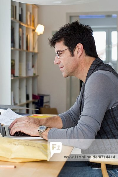 Mature businessman using laptop at home