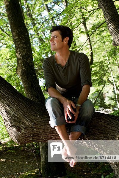 Mature man sitting on tree trunk in forest
