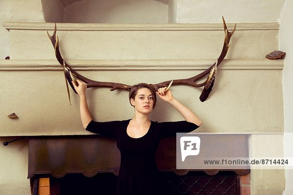 Portrait of young woman standing in front of antlers