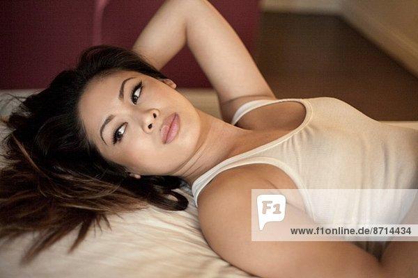 Junge Frau liegt auf dem Bett und schaut zur Seite.