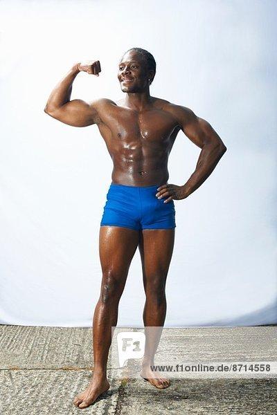 Studio shot of male bodybuilder flexing muscles