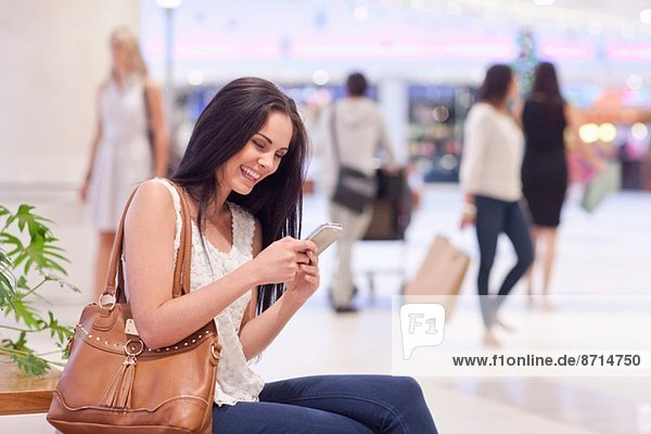 Young woman using cellular phone in mall