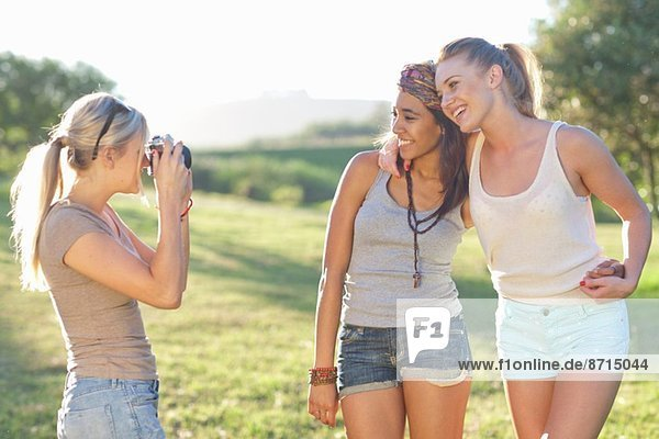 Three young female friends posing for photographs