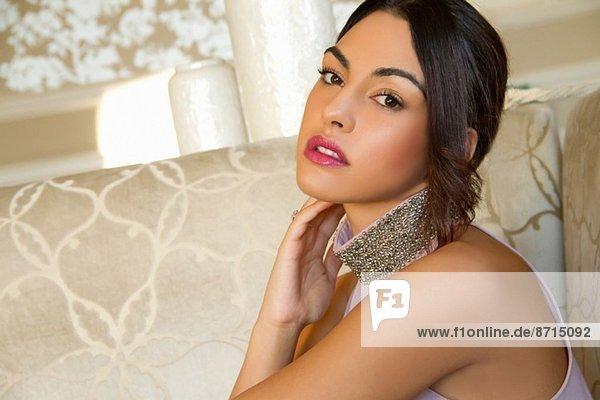 Porträt einer attraktiven jungen Frau auf dem Sofa