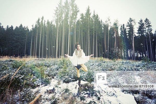 Mittlere erwachsene Frau praktiziert stehende Baum-Yoga-Pose im Wald