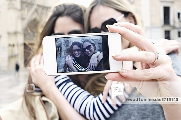 Two young female friends taking a self portrait  Valencia  Spain