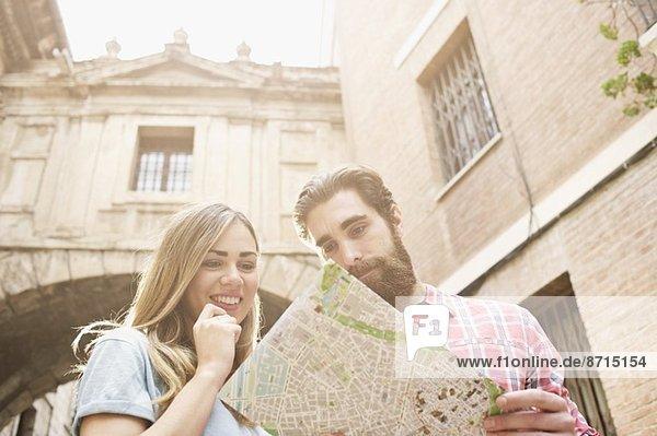 Junges Touristenpaar auf der Karte vor der Kathedrale von Valencia  Valencia  Spanien Junges Touristenpaar auf der Karte vor der Kathedrale von Valencia, Valencia, Spanien