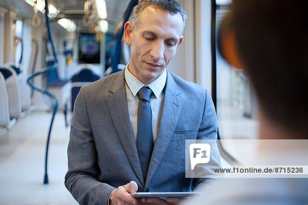 Geschäftsmann mit digitalem Tablett im Zug