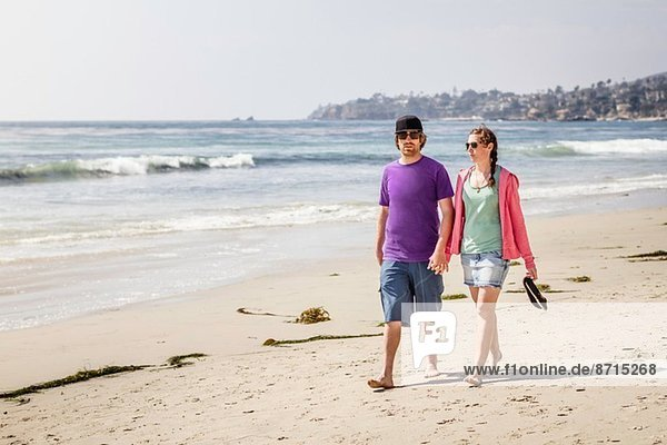 Young couple strolling on beach  Laguna Beach  California  USA
