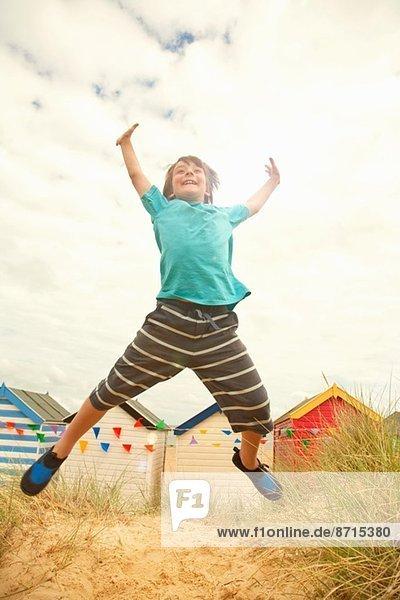 Junge springt in der Luft an der Küste  Southwold  Suffolk  UK