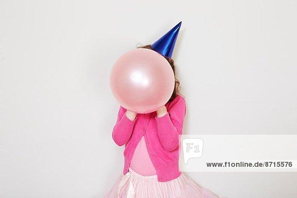 Mädchen hält rosa Ballon vor dem Gesicht Mädchen hält rosa Ballon vor dem Gesicht