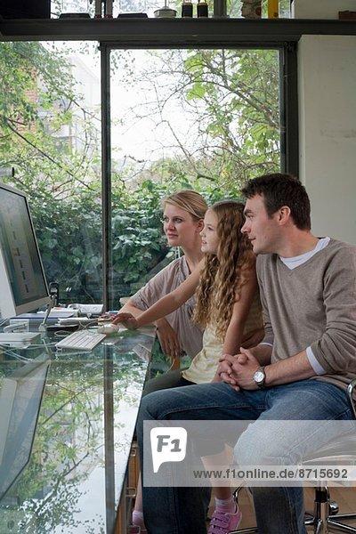 Mädchen und Eltern zu Hause am Computer
