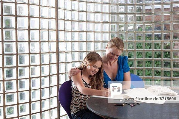 Mädchen und Mutter zu Hause Zeichnen im Skizzenbuch