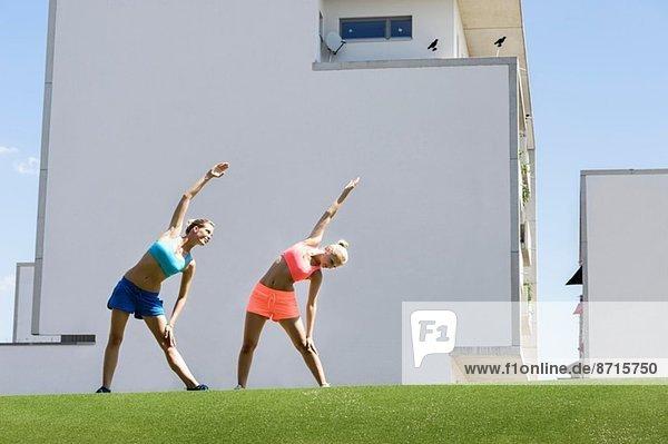 Zwei junge Athletinnen beim Stretching im Park