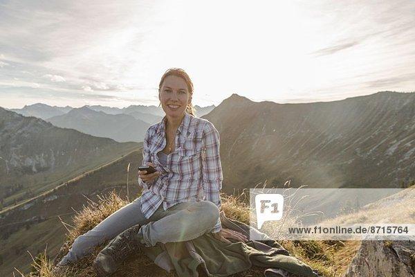 Portrait einer mittelgroßen Backpackerin mit Smartphone  Achensee  Tirol  Österreich