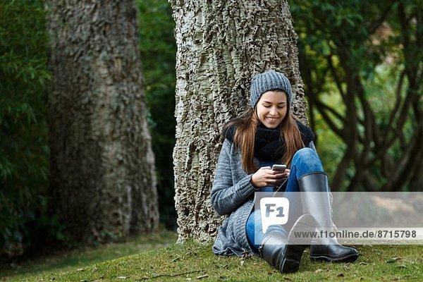 Junge Frau mit Handy im Wald