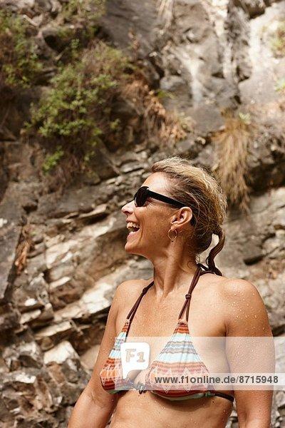 Reife Frau im Bikini und Sonnenbrille lachend
