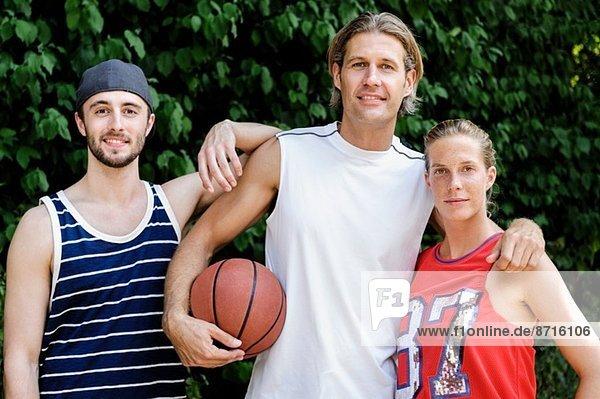Portrait von drei Basketballspielern im Park