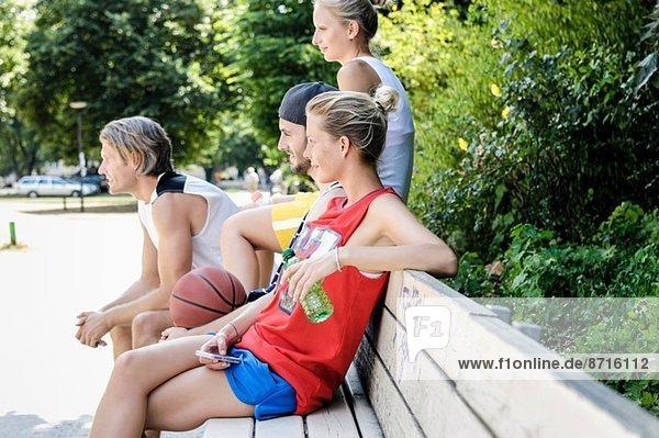 Gruppe von Basketballfreunden bei einer Pause im Park